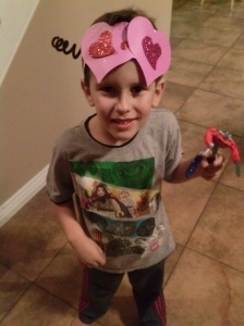 His big brother made the heart crown in his kindergarten class, but Carter models it!